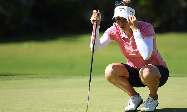 Female golfer looking over putt